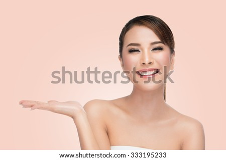 Asian Woman Portrait. Beautiful Spa Girl showing empty copy space on the open hand palm for text. Proposing a product. Skin Care Concept. on pink with clipping path