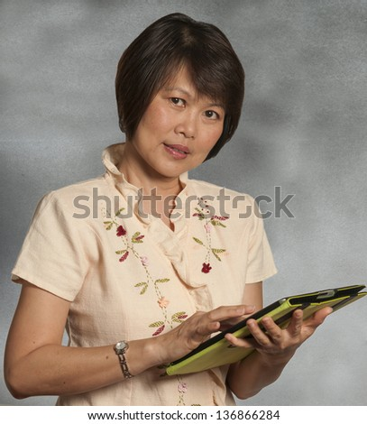 Asian woman portrait with computer tablet - stock photo