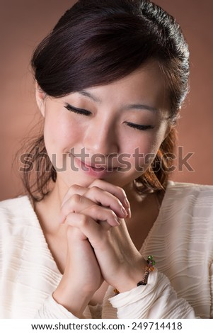 Asian woman praying, closeup portrait on studio brown background. - stock photo