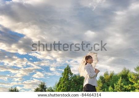Asian woman putting up a parasol - stock photo