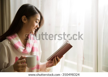 Asian woman reading a book and drinking coffee in the morning. - stock photo