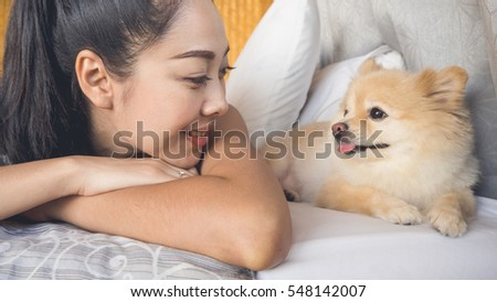 Asian woman relax on bed with her dog in bamboo bedroom.