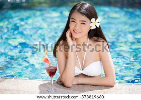 Asian woman relaxing in a swimming pool. She is wearing a bikini - stock photo