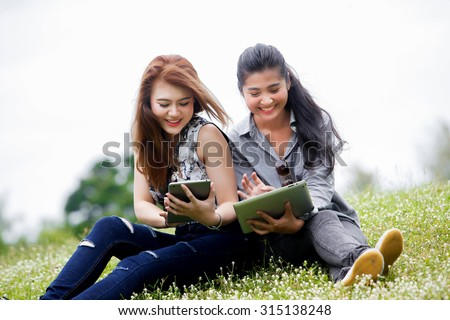 asian woman relaxing in the park and reading her tablet for business and vacation