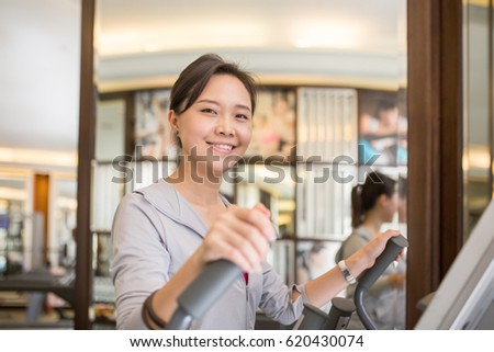 Asian woman running inside fitness room.