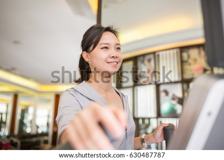 Asian woman running with machine walking in fitness room.