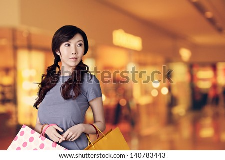 Asian woman shopping and looking at modern mall with copyspace.