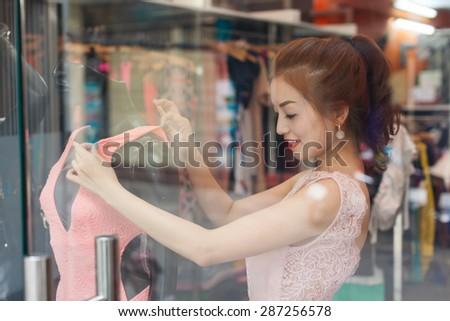 Asian woman shopping choosing fashion dress shop window - stock photo
