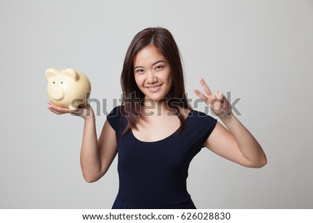 Asian woman show victory sign with pig coin bank on gray background
