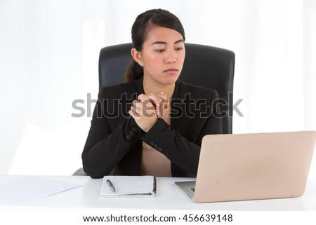 Asian woman sitting at the desktop working on her laptop.