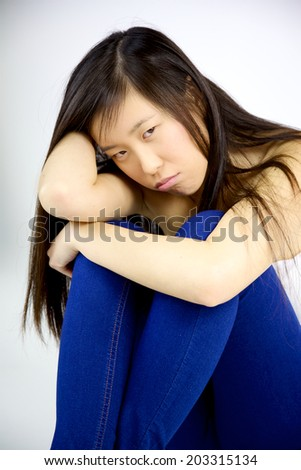 Asian woman sitting isolated feeling depressed and bored