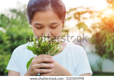 Asian woman smelling flowers in garden. - stock photo