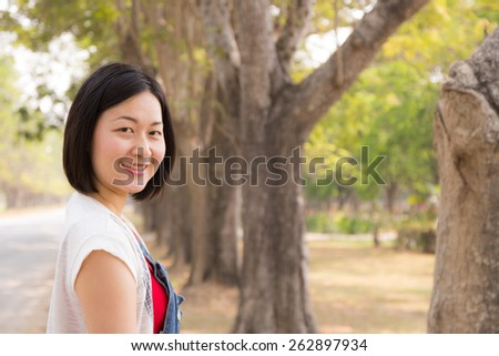 Asian woman Smile face close up and she  in the morning with nature green background, model is a asian girl - stock photo