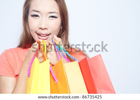 Asian woman smiling and holding colorful shopping bags