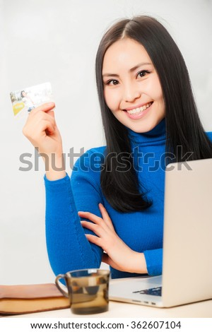 Asian woman smiling and holding her credit card.