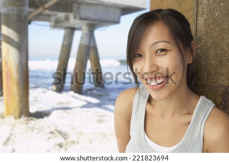 Asian woman smiling near pier at beach - stock photo
