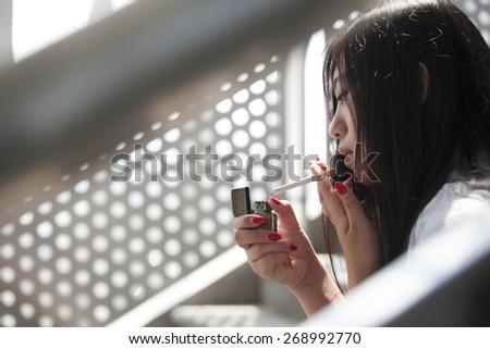 Asian woman smoking - stock photo