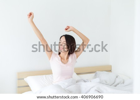 Asian Woman stretching hand on bed - stock photo