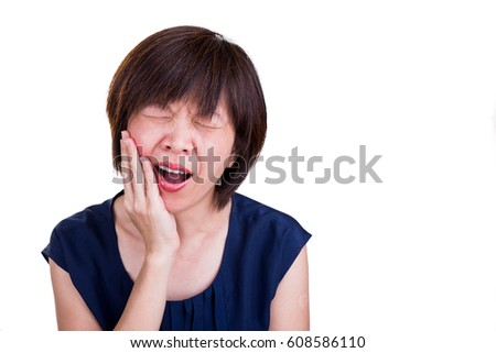 Asian woman suffering intense toothache pain with hands over face with white background