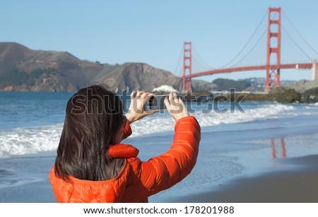 Asian woman taking pictures at golden gate bridge - stock photo