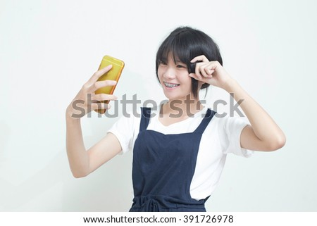 Asian woman taking pictures of themselves with a mobile phone. - stock photo