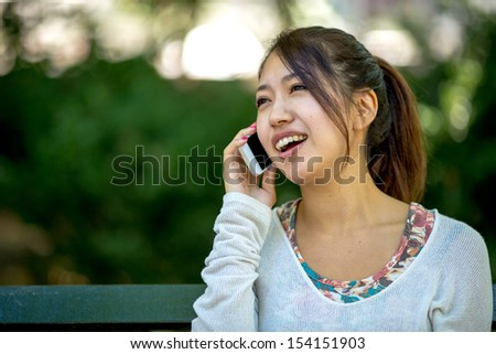 Asian woman talking on iphone ellphone outdoor