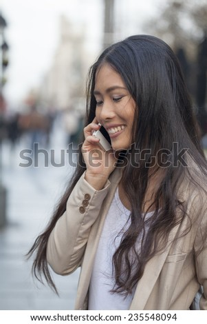 Asian woman talking on mobile phone - stock photo