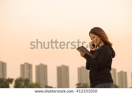 Asian woman talking on phone and holding tablet with sunset sky background - stock photo