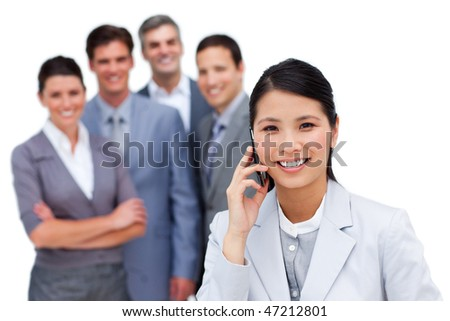 Asian woman talking on phone in front of her team against a white background