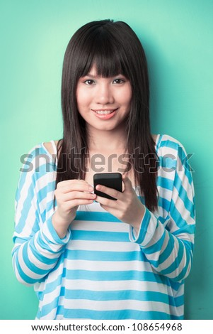 Asian Woman texting on her cell phone leaning against a green wall. - stock photo