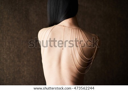 Asian woman: the back of a Chinese woman wearing a gold necklace. sensuality, poise , pride.