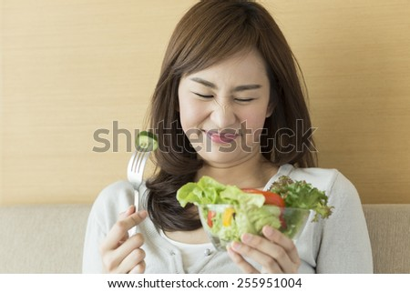 Asian woman trying to eat healthy salad. - stock photo