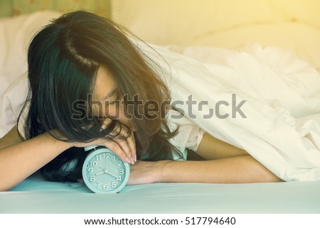 Asian woman trying to sleep, when alarm clock ringing.