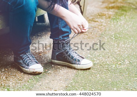 Asian woman tying her shoes. vintage style effect picture. - stock photo