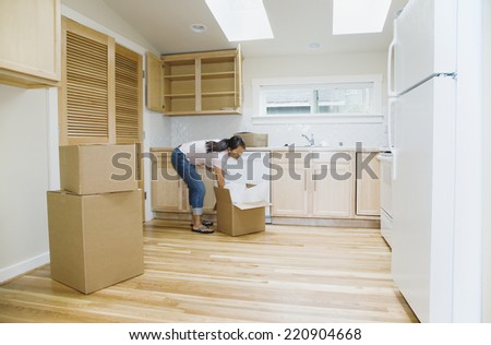 Asian woman unpacking boxes in new house - stock photo
