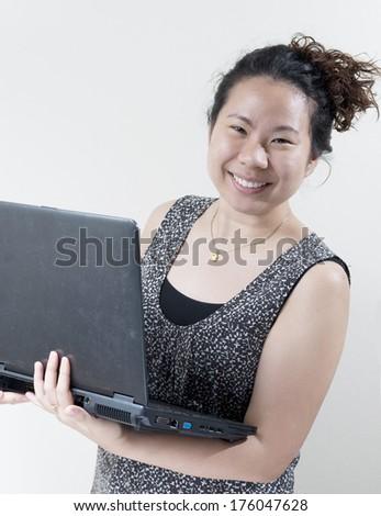 Asian woman using a laptop - stock photo