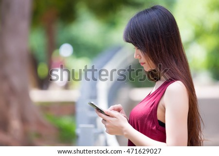 Asian woman using a smart phone while waiting for the bus. Summer