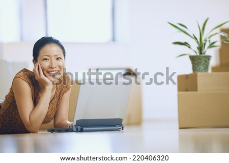 Asian woman using laptop in new house with boxes - stock photo
