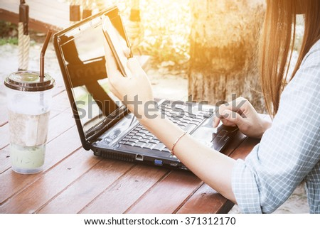 Asian woman using laptop in the coffee shop.