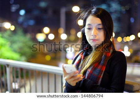 Asian woman using mobile at night - stock photo