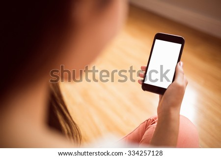 Asian woman using phone with copy space at home in the living room - stock photo