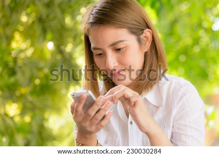 Asian woman using smart phone for communication - stock photo