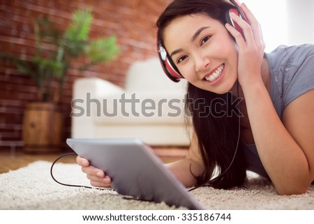 Asian woman using tablet on floor at home in the living room - stock photo