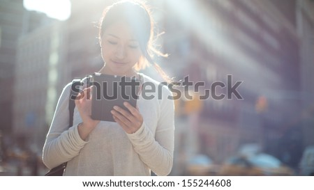 Asian woman using tablet pc computer outdoor on a city street - stock photo