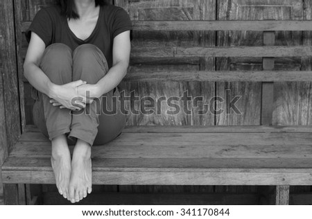Asian woman waiting siting on wooden chair with wall background.