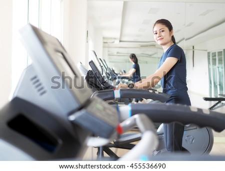 Asian woman walking,  running on treadmill gym workout. - stock photo