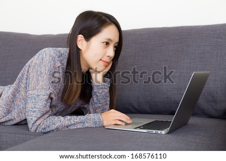 Asian woman watching movie on laptop - stock photo