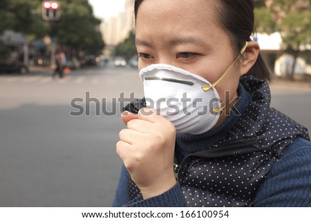 Asian woman wearing a protective face mask on a city street with air pollution - stock photo