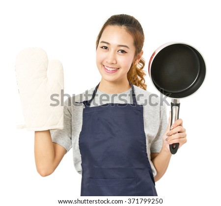 Asian Woman Wearing Apron And Showing Pot With Oven Glove - stock photo