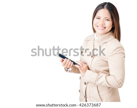 asian woman wearing brown coat and holding tablet isolated on white